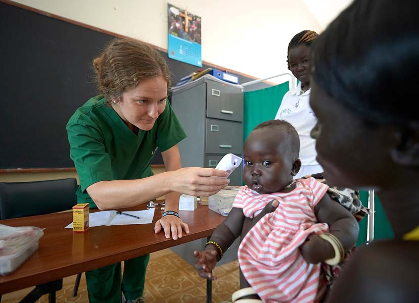 Nicky Hess, a Mennonite volunteer from the United States, checks a child's temperature in the clinic of the Loreto School in Rumbek, South Sudan. The school is run by the Institute for the Blessed Virgin Mary--the Loreto Sisters--of Ireland. Hess is an emergency room nurse from Lancaster, Pennsylvania.