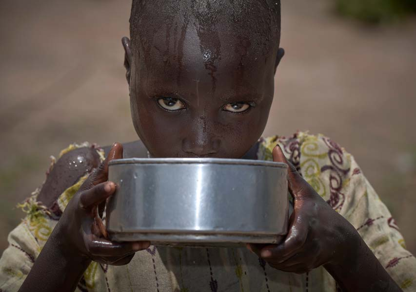 A girl drinks water in an emergency feeding program for malnourished children at the Loreto School in Rumbek, South Sudan. The school, run by the Institute for the Blessed Virgin Mary--the Loreto Sisters--of Ireland, has opened its compound to hundreds of nearby villagers facing hunger because of ongoing conflict and climate change.