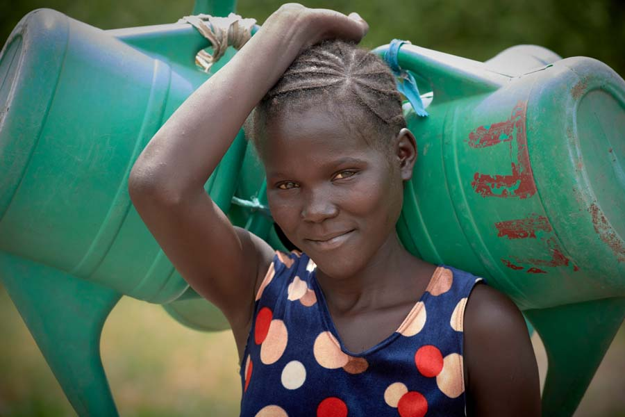 A woman from the village of Maker Kuei carries watering cans on her way to irrigate the vegetable garden of the Loreto Girls Secondary School outside Rumbek, South Sudan. The school is run by the Institute for the Blessed Virgin Mary--the Loreto Sisters--of Ireland.